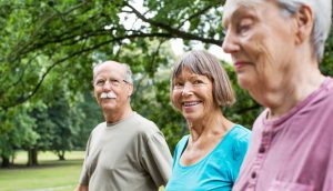 Three seniors walking in a park
