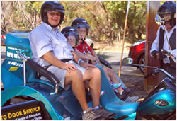 A volunteer and two children sat on a motorcycle trike at the Ella's House Respite Centre fete
