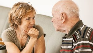 A middle-aged woman having a conversation with her elderly father about dementia