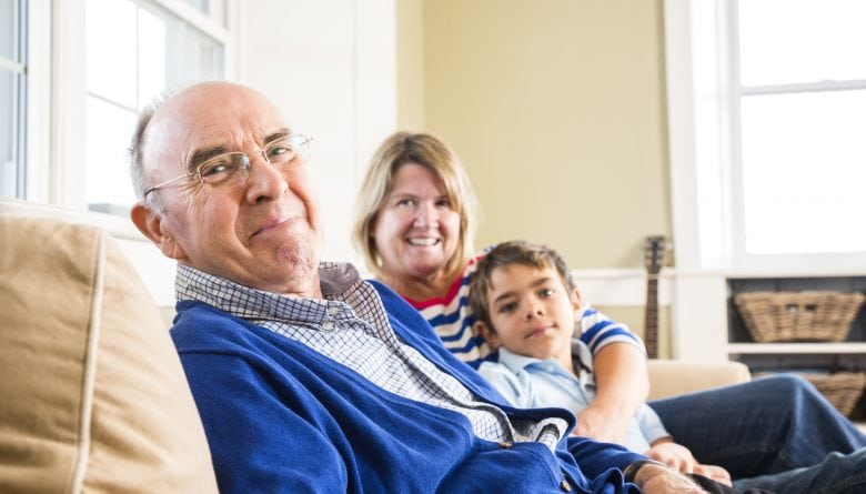 Elderly man in blue sweater with family on sofa