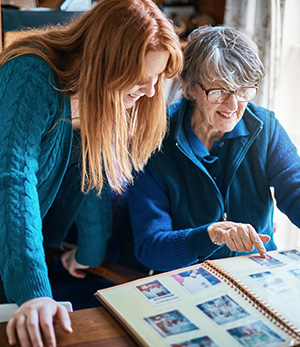 Elderly lady and daughter looking at old family photos