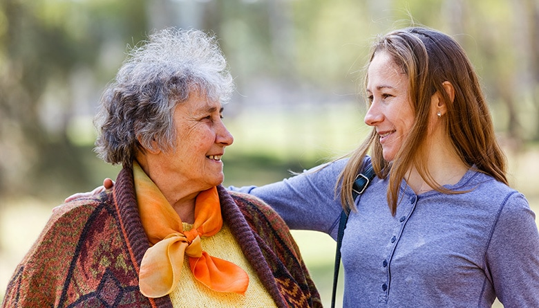 Carer and senior woman outdoors